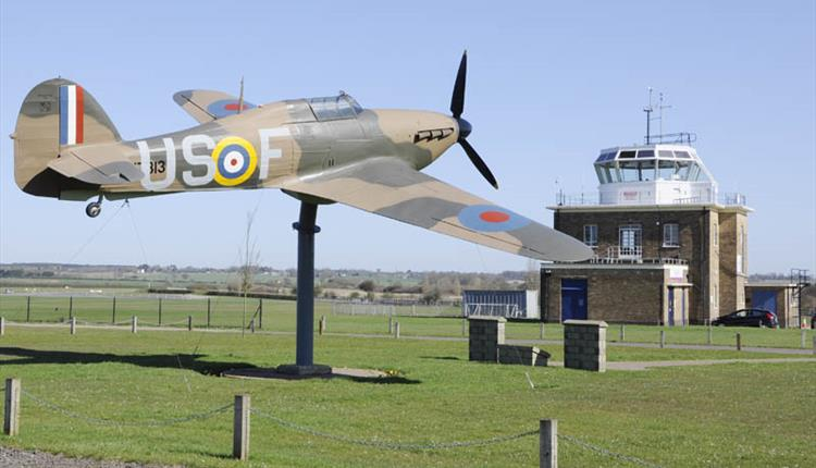 "The Hurricane ""Gate-Guardian"" at North Weald Airfield with control tower in the background."
